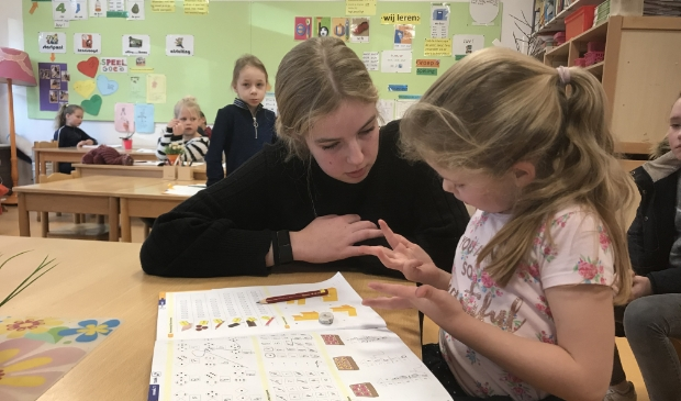Kim van Hamersveld helpt leerlingen in groep 3/4 met rekenen.