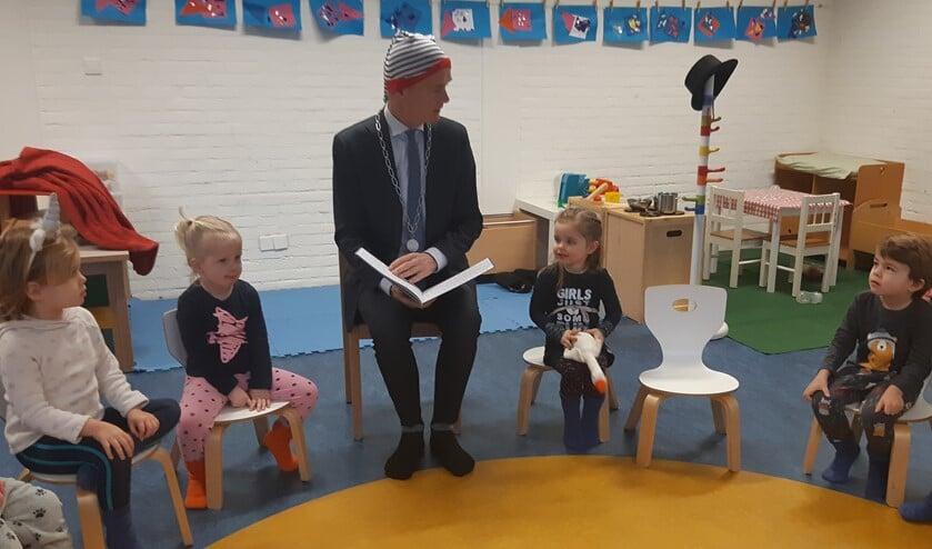 Burgemeester Niek Meijer leest met een slaapmuts op voor aan de kinderen bij Peuterschool 't Startbloek.
