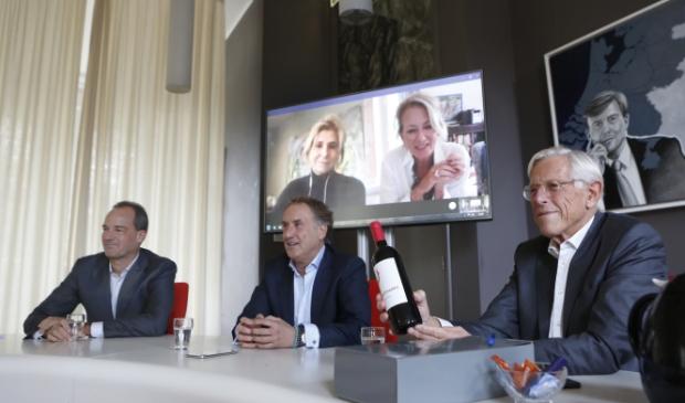 <p>Wethouder Stam toont te gewonnen fles wijn aan winnares Lisette.</p>
