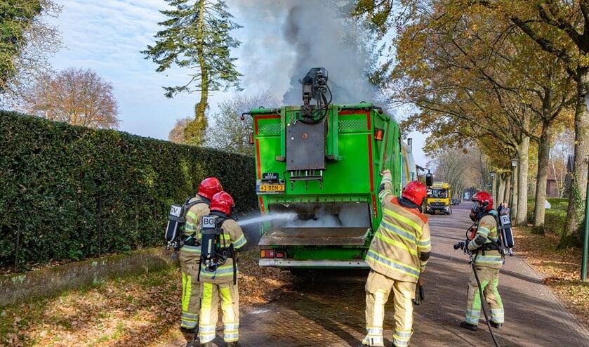 <p>De brandweer probeert de brand in de vuilcontainerwagen te blussen.</p>
