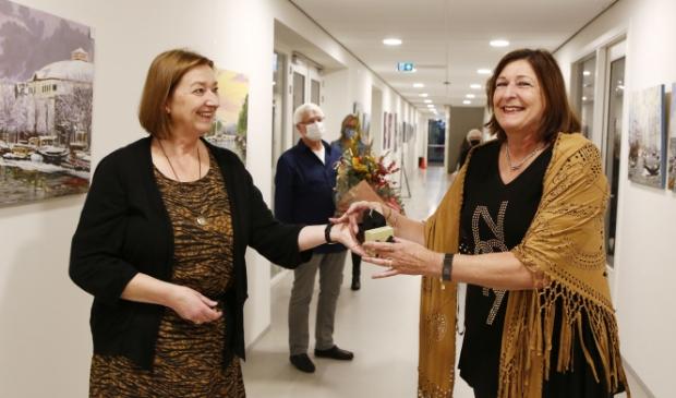 <p>Wethouder Wilma de Boer-Leijsma (l) reikt de erespeld uit aan Monique Kropman in het Huis van Eemnes.</p>