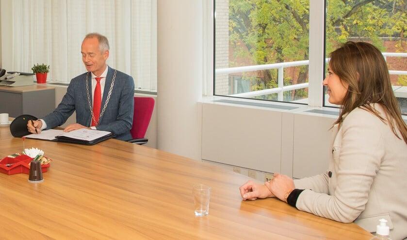 <p>Burgemeester Niek Meijer zet zijn handtekening onder het convenant.</p>