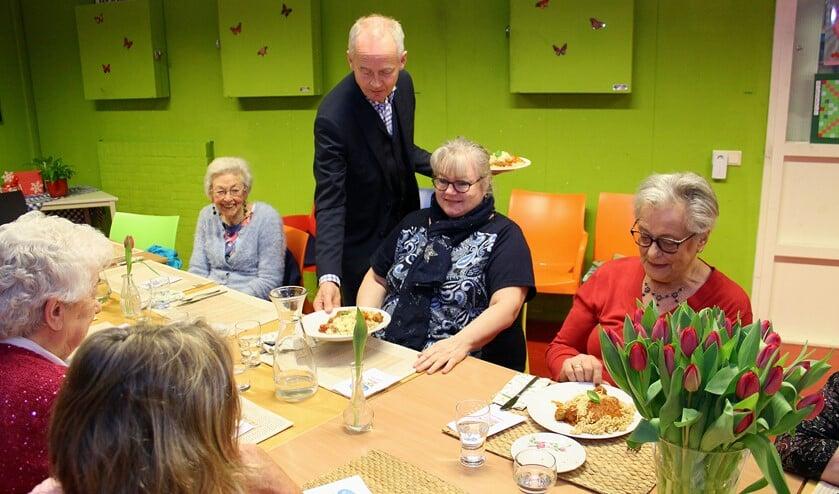 Als een volleerd butler serveerde de burgemeester de maaltijden.