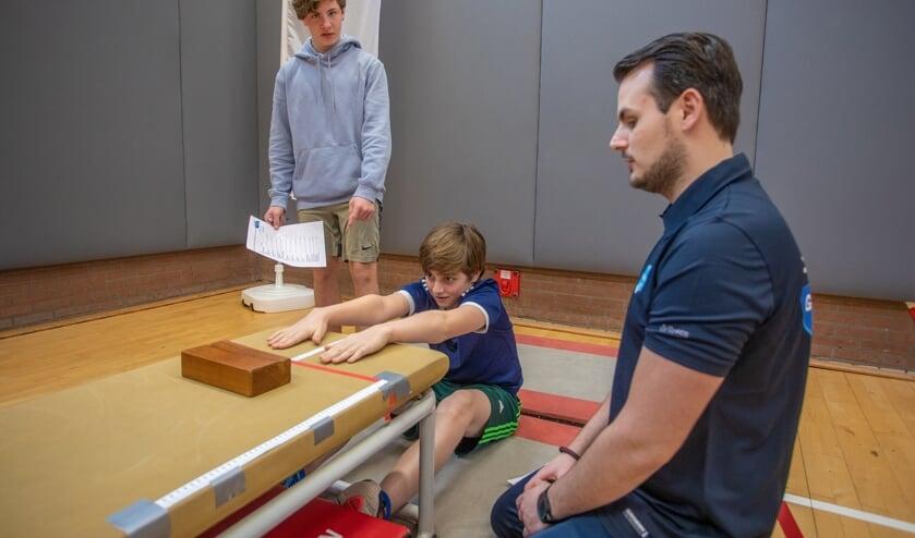 Patrick kijkt toe hoe twee leerlingen een test voor lenigheid afnemen in de gymzaal.