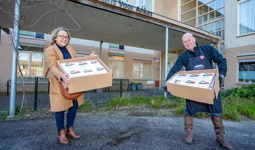 Personeel van Voor Anker neemt op gepaste afstand de koeken in ontvangst van Jan Koelewijn van 't Stoepje.