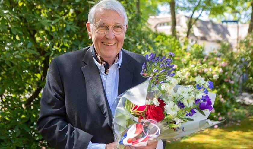 Teun Koetsier met zijn bloemen, die hij kreeg uit handen van de burgemeester vanwege zijn koninklijke onderscheiding.
