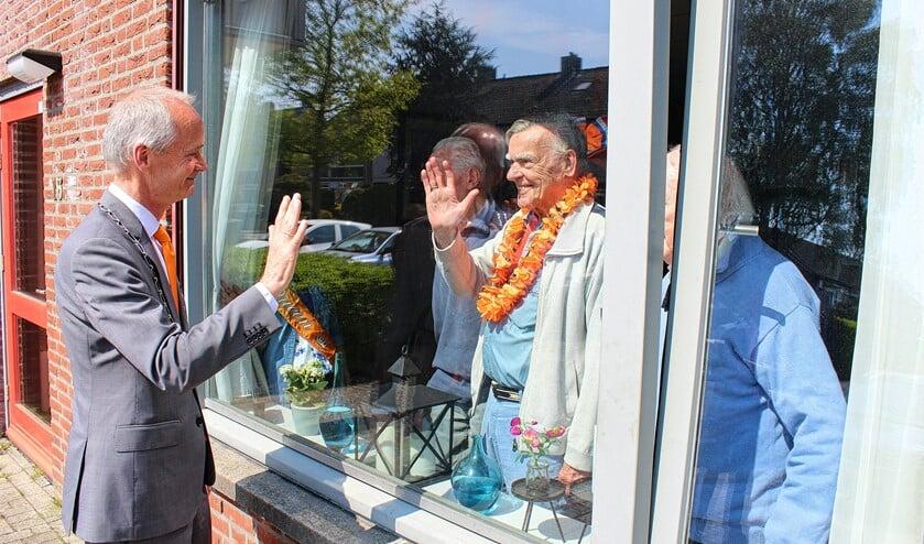 Burgemeester Niek Meijer zwaait naar bewoners.