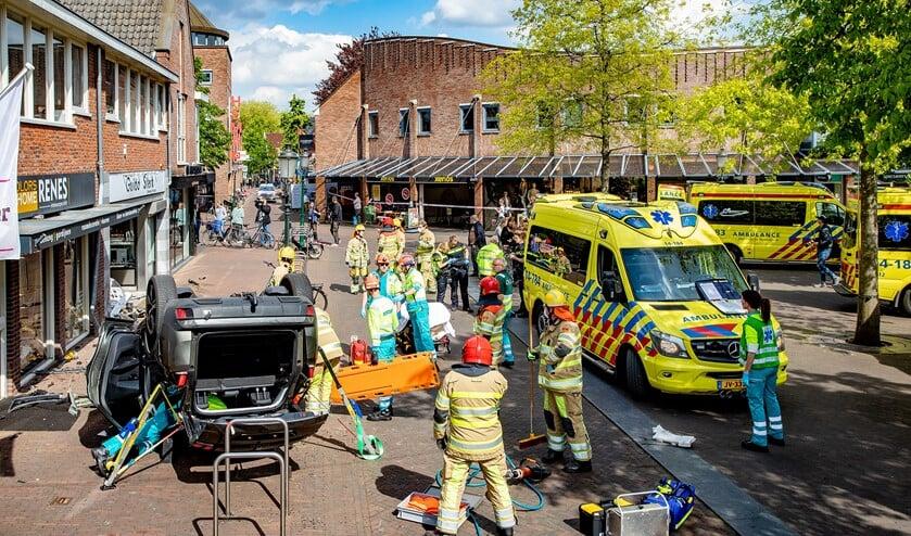 Hulpverleners ter plaatse om de beknelde bestuurder uit zijn auto te halen.