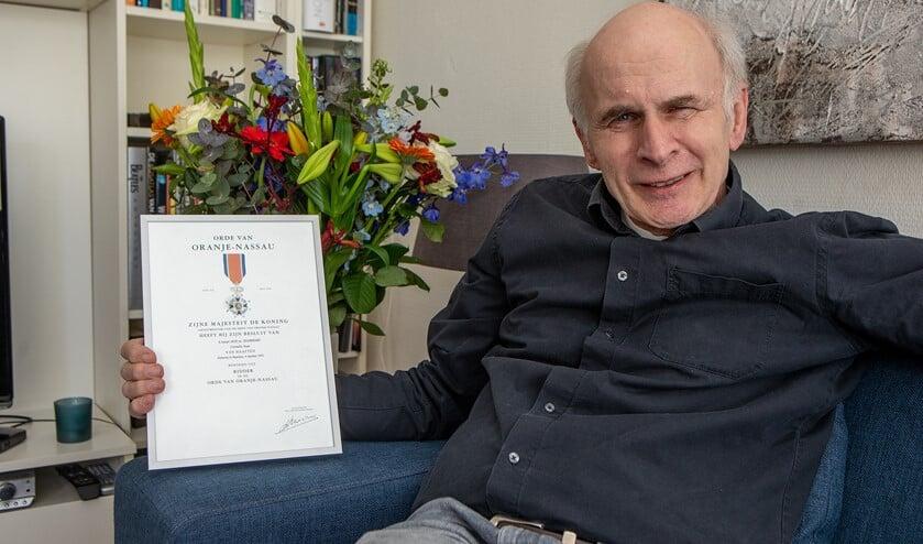 Joan van Haaften met zijn kopie van de oorkonde en bos bloemen die hij kreeg vanwege zijn onderscheiding.