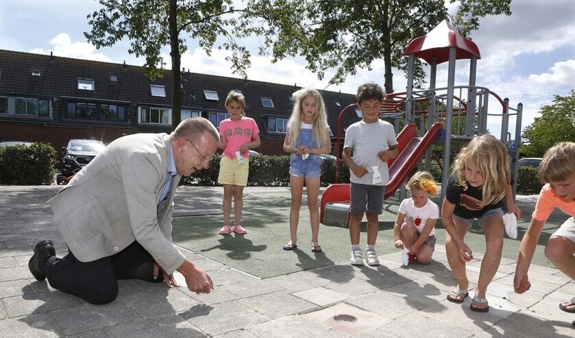 Wethouder Theo Reijn knikkerde met de kinderen, die een zakje knikkers cadeau hebben gekregen van de gemeente.