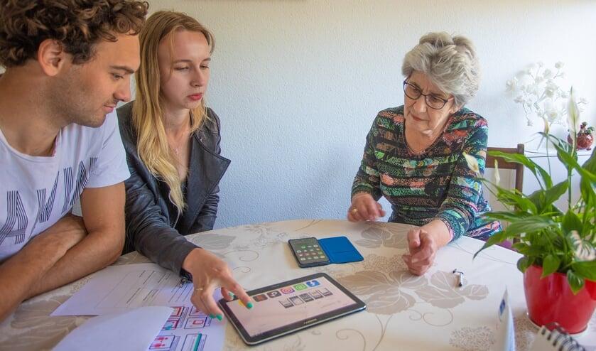 Vrijwilligers brengen een tablet bij Ditte van Doorn.