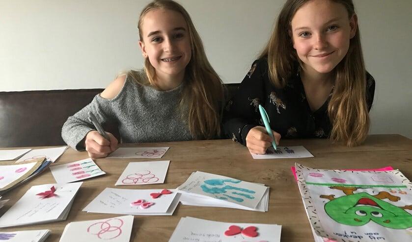 De zusjes Jinte en Fenne met hun zelfgemaakte kaarten.