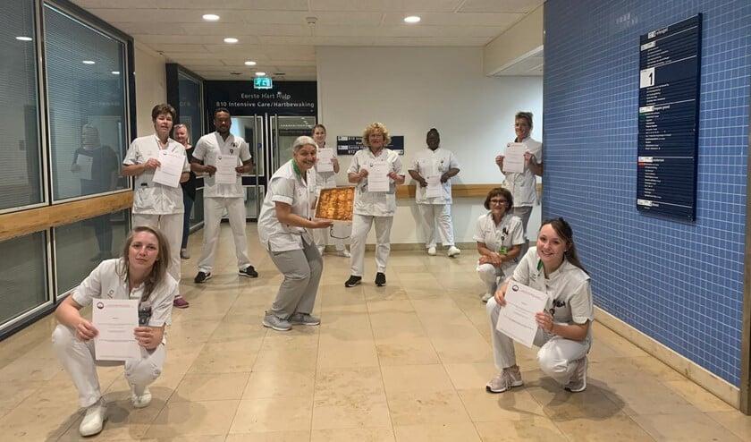 Medewerkers van het ziekenhuis in de gang met de cake en bedankbrief.