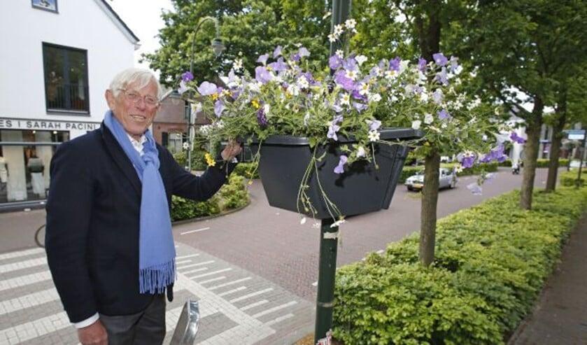 Wethouder Ton Stam bevestigt één van de hanging baskets in het centrum van Laren.