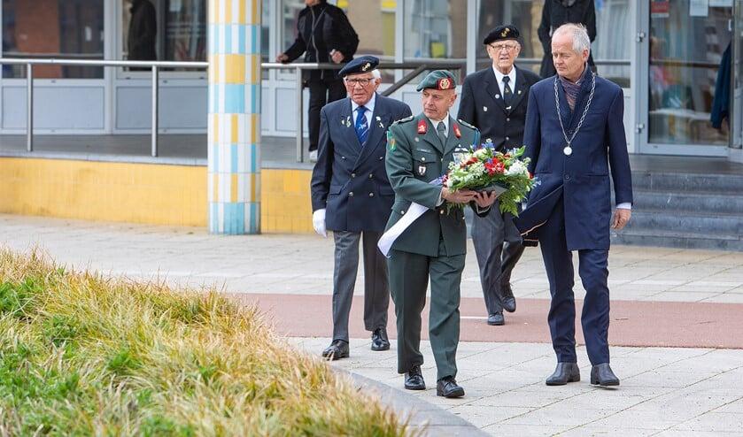 Veteranen leggen samen met de burgemeester bloemen neer bij het monument.