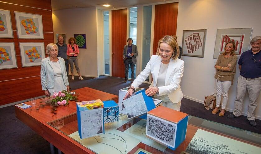 Wethouder Karin van Hunnik bouwt een eigen kunstwerk als opening van de tentoonstelling.
