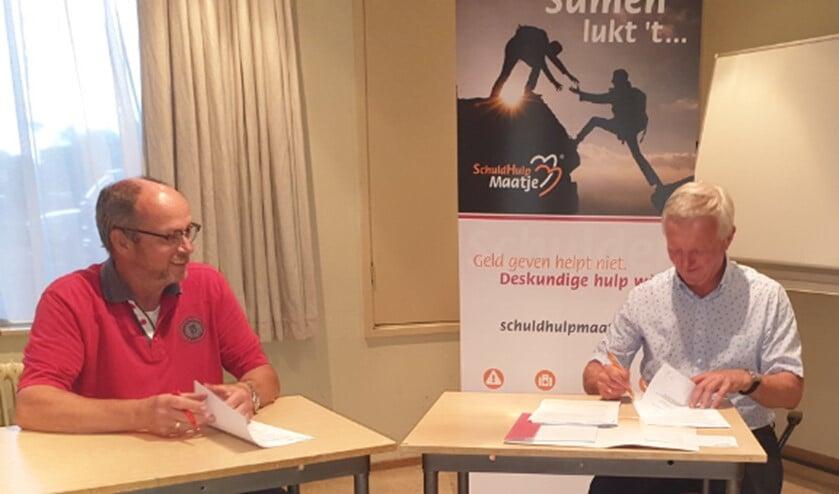 Jan Otter (l) en Gerard Barmentlo ondertekenen de overeenkomst met SchuldHulpMaatje Nederland.
