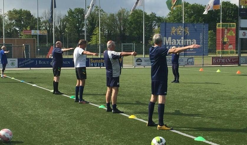 De warming-up bij Walking Football op 1,5 meter afstand van elkaar.