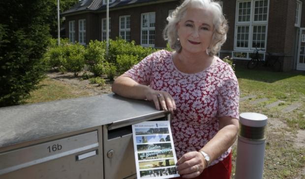 Burgemeester Joan de Zwart-Bloch met de ansichtkaart met vragen die alle inwoners krijgen.