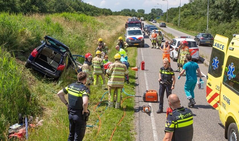 Hulpverleners ontfermen zich over de bestuurster die met haar auto uit de bocht was gevlogen.