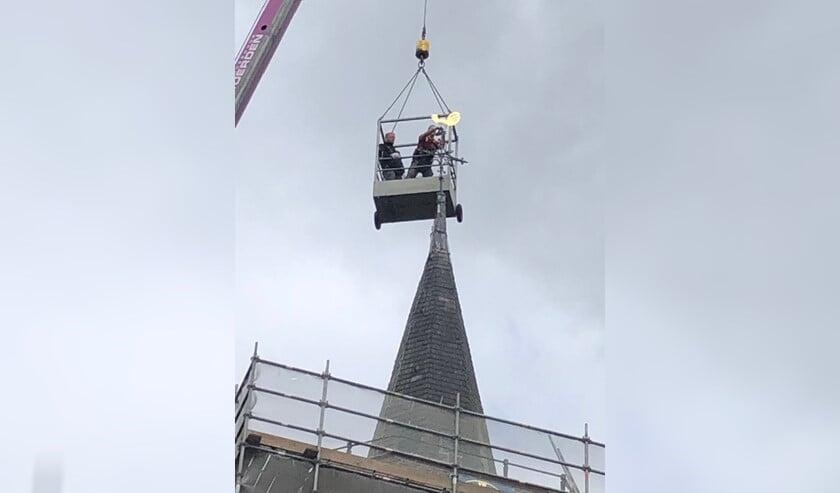 Al wiebelde de gondel door de stevige wind op 30 meter hoogte, de haan werd keurig teruggeplaatst.