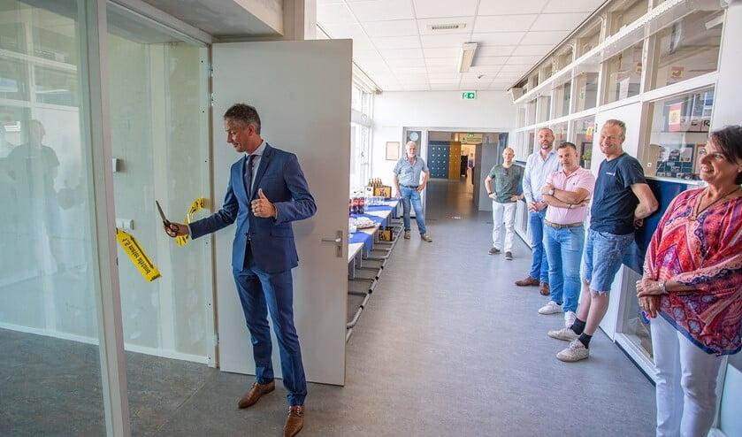 Bart van den Haak knipt het lint door in aanwezigheid van de bouwers en rector Loes IJkelenstam.