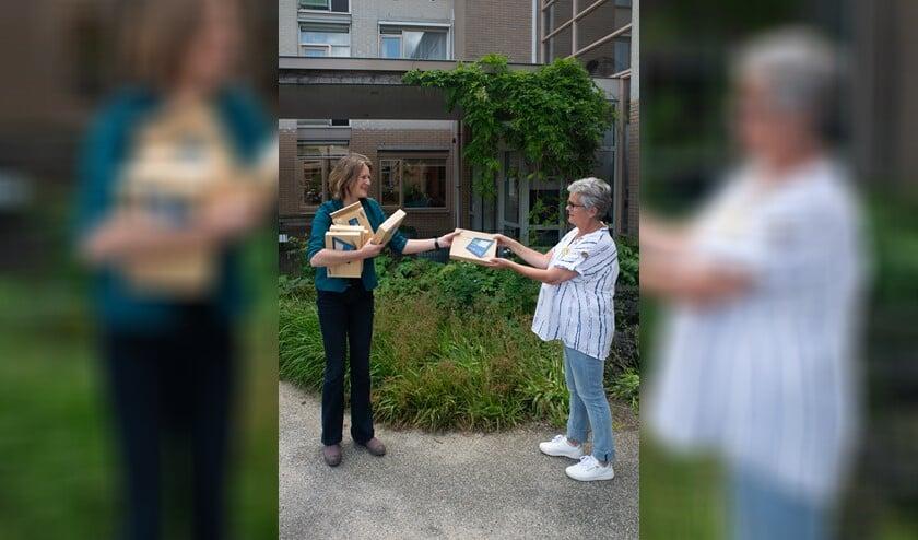 Anneke van der Veer van Versa Welzijn overhandigt de tablets aan Greet Kos.