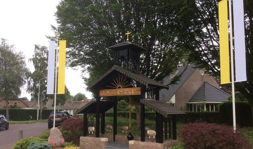 De geel met witte vlaggen wapperen bij de Goede Herder Kapel.