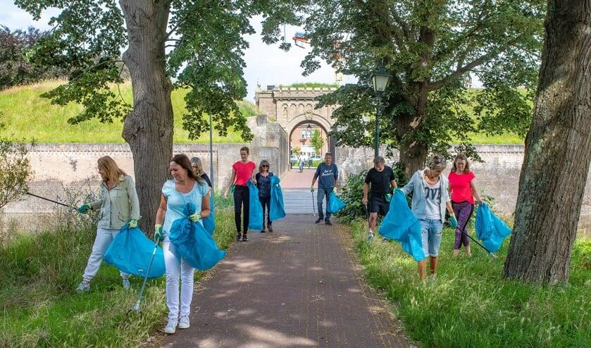 Met grijpers, handschoenen en vuilniszak gaan inwoners aan de slag het zwerfvuil op te ruimen.