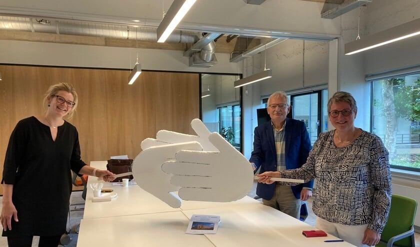 Anne Oosterbaan (l) van de Alliantie, Sytze Haenen en Jacobien Middelkoop feliciteren elkaar op 1,5 meter met de overeenkomst.