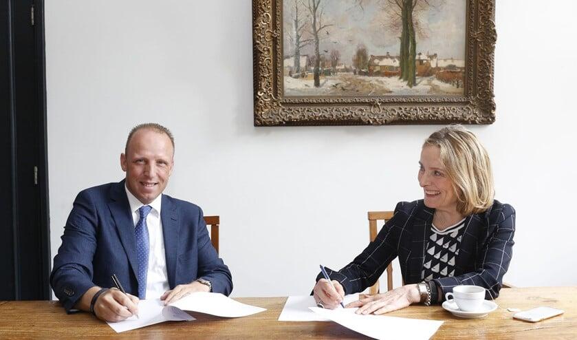 Wethouder Karin van Hunnik (r) tekent de stukken.