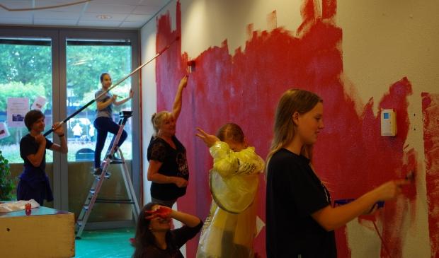 De jongeren schilderen een van de muren rood, een kleur die in het hele wijkcentrum terugkomt.