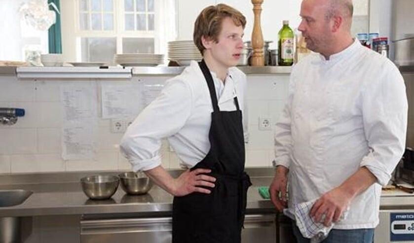 <p>Kok Robbert Jan met een van de leerlingen in de keuken van het Papagenohuis.</p>