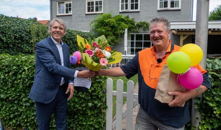Wethouder Nico Schimmel overhandigt de bos bloemen aan postbode Peter Bakker