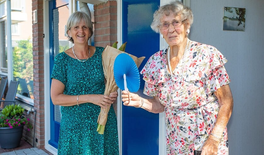 <p>Manon Vanderkaa (l) waaide ook bij mevrouw Beekman-van der Born aan met een blauwe waaier en bos bloemen.</p>