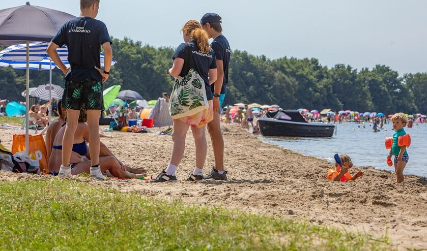 <p>De Junior Strandwachten in gesprek met ouders op het strand.</p>