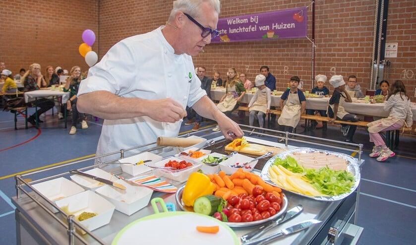 Tv-kok Rudolph van Veen hielp de leerlingen met het maken van een gezonde broodrol.
