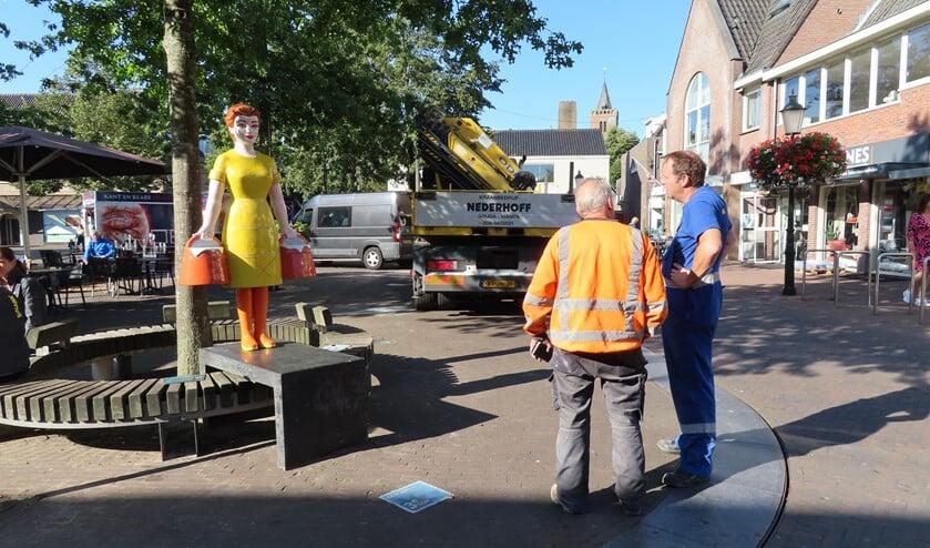 De heren die het beeld hebben geplaatst, inspecteren hun werk.