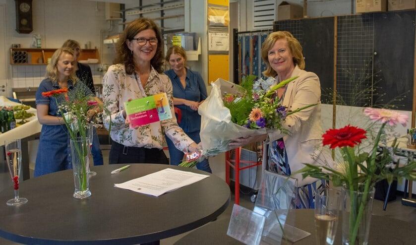 Wethouder Marlous Verbeek (r) feliciteert rector Tanja de Ruijter met het certificaat.