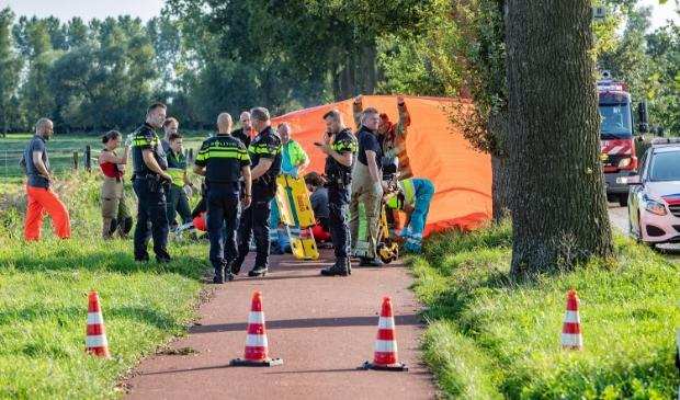 <p>De brandweer bekommert zich met ambulancepersoneel om de fietser.</p>