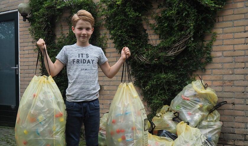 <p>Tim van der Lugt (8) met zijn 9 zakken plastic flessen die hij het afgelopen jaar heeft verzameld.&nbsp;</p>