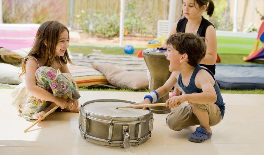 three kids in the backyard having fun with drums.