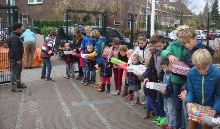 Toen alle dozen op school waren ingeleverd,maakten alle leerlingen een lange rij om ze uiteindelijk allemaal in de grote kar te krijgen.