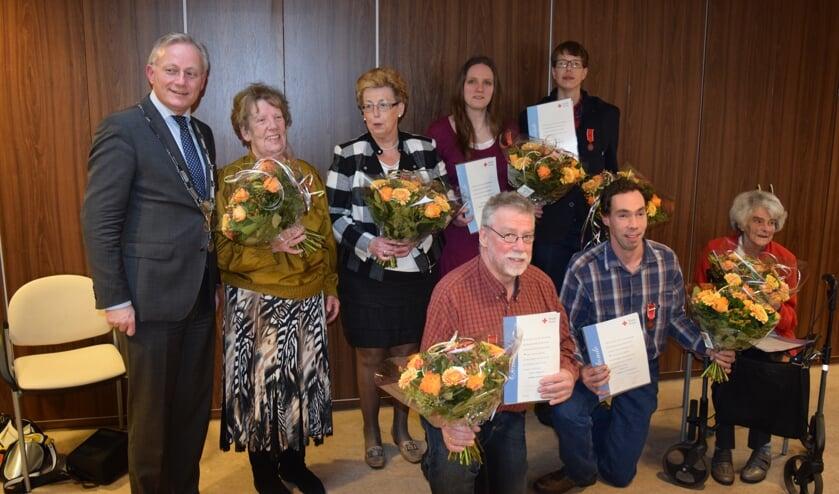 De onderscheiden vrijwilligers naast burgemeester Arjen Gerritsen.