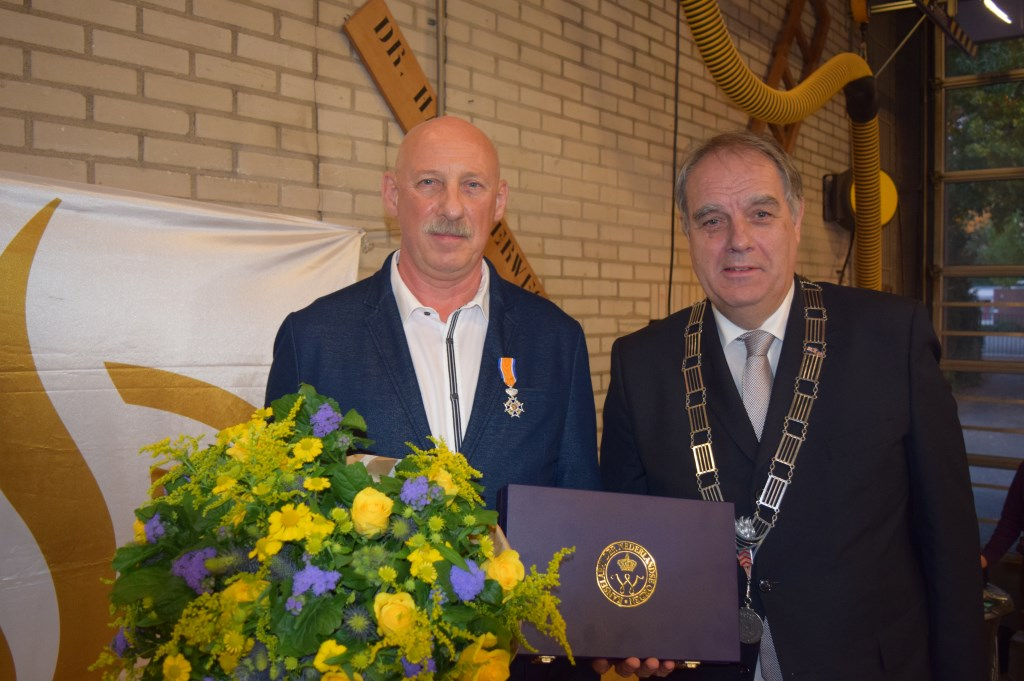 Vrijwillige brandweerman Frans van den Berg uit Bilthoven krijgt vanwege zijn verdiensten door wnd. burgemeester Bas Verkerk de versierselen, behorend bij zijn benoeming tot Lid in de Orde van Oranje-Nassau, opgespeld.  © De Vierklank