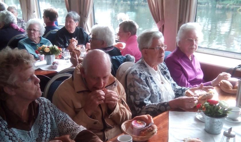 Zonnebloemgasten genieten aan boord van de lunch.
