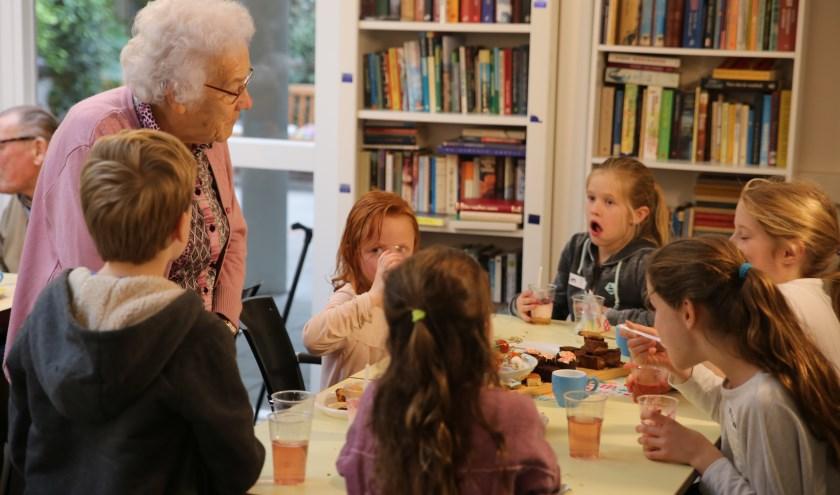 De bakkers smikkelen mee tijdens de high tea voor ouderen.