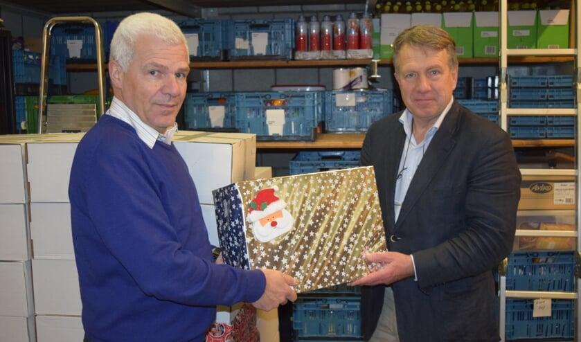 Klaas Kuiken (r) overhandigt het eerste kerstpakket aan Rob Veerman.