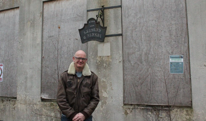 Jeroen van den Berg voor de vervallen Smederij Vervat in Lage Vuursche. Op een uithangbord staat te lezen 'Anno 1854 smederij G. Vervat'.