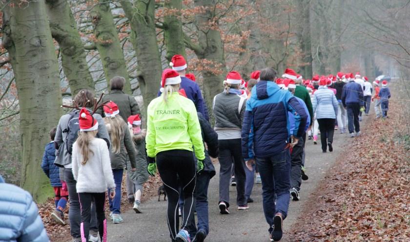 Zo'n 75 kerstmutsen vinden hun weg door het bos.